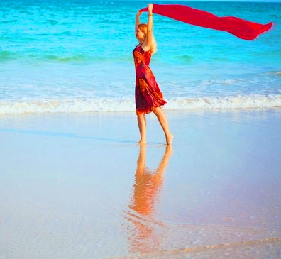 Woman in Bright Red Sarong and Scarf Walking along the Beach